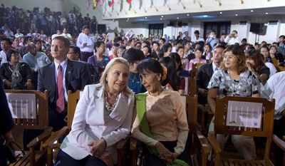 U.S. Secretary of State Hillary Rodham Clinton (left in foreground) and Myanmar opposition leader Aung San Suu Kyi sit together before President Obama speaks Nov. 19, 2012, at University of Yangon in Yangon, Myanmar. (Associated Press)