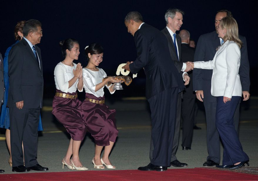 President Obama is given flowers as he and U.S. Secretary of State Hillary Rodham Clinton (right) arrive on Air Force One at Phnom Penh International Airport in Phnom Penh, Cambodia, on Nov. 19, 2012, to attend the East Asia Summit. (Associated Press)