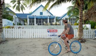 """A man rides his bicycle past the beachside entrance to the home of software company founder John McAfee in Ambergris Caye, Belize, on Thursday. Mr. McAfee has been identified as a """"person of interest"""" in the killing of Gregory Viant Faull, his neighbor. (Associated Press)"""