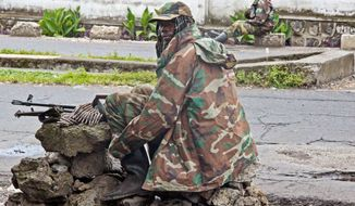 An M23 rebel soldier looks back as he and others take positions near the Heal Africa hospital in the center of Goma on Tuesday. A rebel group created just seven months ago seized the strategic provincial capital of Goma. (Associated Press)