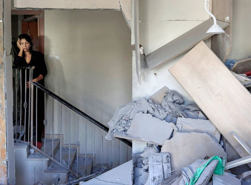 An Israeli woman examines the damage to her Beersheba home, which was hit Tuesday by a rocket fired by militants from the Gaza Strip. Both sides ratcheted up attacks in anticipation of a cease-fire that failed to take hold. For the first time since fighting erupted a week ago, a Hamas rocket hit an apartment building in metropolitan Tel Aviv. Residents escaped injury by taking shelter in specially fortified rooms. (Associated Press)