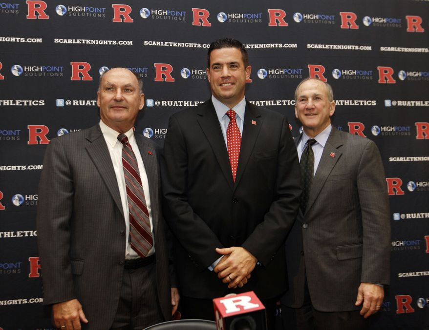 Rutgers Director of Intercollegiate Athletics Tim Pernetti, center, stands with Rutgers President Robert Barchi, right, and Big Ten Conference Commissioner Jim Delany during a news conference, Tuesday, Nov. 20, 2012, in Piscataway, N.J., after they  announced that Rutgers will join the Big Ten. Rutgers will join the conference in all sports at a date to be determined. (AP Photo/Mel Evans)