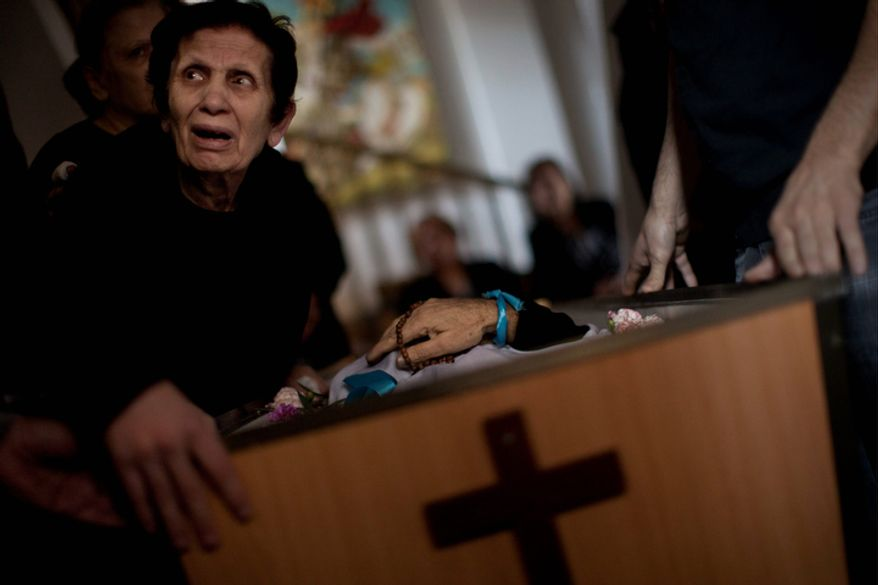 A Palestinian mourner cries during the funeral of Salem Paul Sweliem in Gaza City on Nov. 20, 2012. According to the family, the 52-year-old Greek Orthodox Christian carpenter was killed during an Israel Air Force strike on a high-rise building, in which Ramez Harb, a senior figure in Islamic Jihad's military wing, was killed. Sweliem was in car when the strike took place and died on his way to the hospital from shrapnel wounds. (Associated Press)