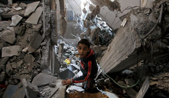 A Palestinian boy stands Nov. 20, 2012, in the rubble left after an Israeli strike on a house in Gaza City. (Associated Press)