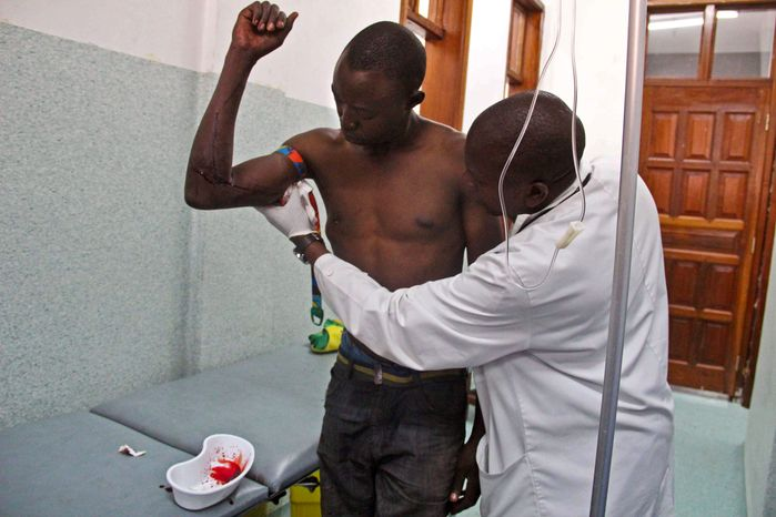 A young man (left) wounded by bullets during fighting between the Congolese army and M23 rebels is treated at the Heal Africa hospital in Goma, Congo, on Nov. 20, 2012. (Associated Press)