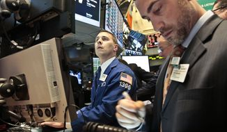 Joseph Mastrolia (left), a trader with Barclays, and Chris Casaliggi, Euronext floor manager, begin early trading on the floor of the New York Stock Exchange on Nov. 20, 2012. (Associated Press)