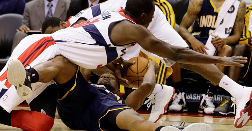 Washington Wizards center Earl Barron (top) dives for the ball as Indiana Pacers forward Sam Young holds on to it during the first half of the Pacers' 96-89 road win on Nov. 19, 2012. (Associated Press)