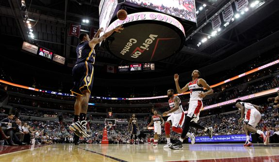 Indiana Pacers guard George Hill shoots as Washington Wizards forward Trevor Booker (center left) and guard Shaun Livingston can't reach him in time during the second half of the Pacers' 96-89 road win on Nov. 19, 2012. (Associated Press)