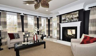 The family room has a fireplace flanked by windows.
