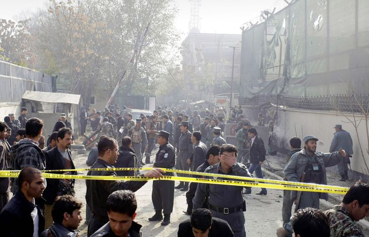 associated press  Afghan security men and media members gather at the scene of a suicide attack in Kabul, Afghanistan, on Wednesday. A man wearing a suicide vest blew himself up near a U.S. base in the capital early Wednesday. Two guards were killed.