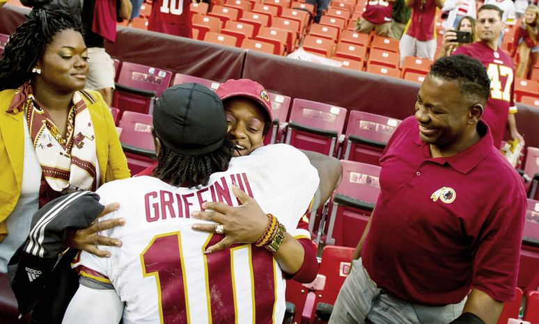 Redskins quarterback Robert Griffin III hugged his mother, Jacqueline, as sister Dejon (left) and father Robert Griffin Jr. looked on after an exhibition game in August. Family interaction always was stressed in the Griffin household. (Andrew Harnik/The Washington Times)