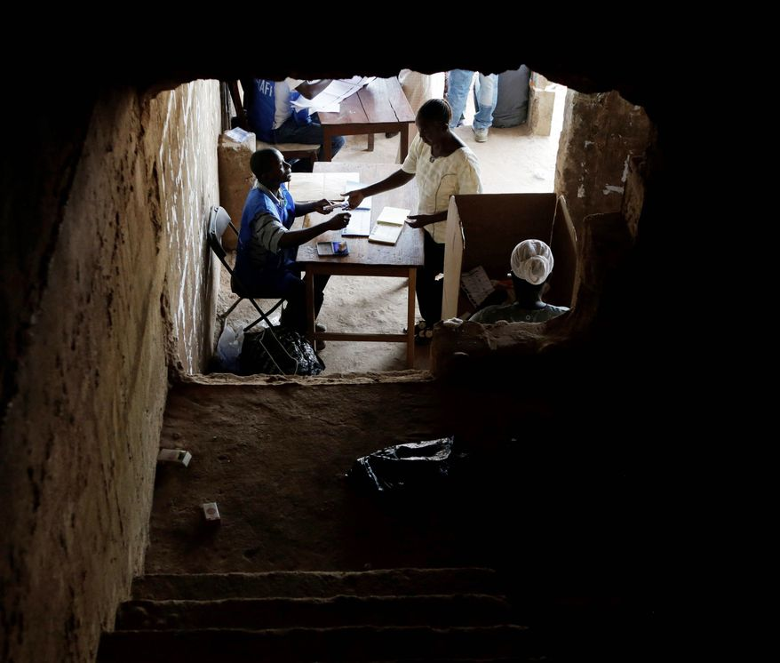 A voter presents identification at a polling station located in an unfinished building in Freetown. (Associated Press)