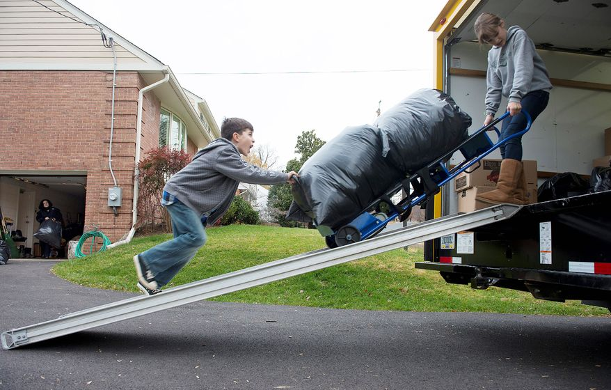 Andrew Audas, 9, and his sister Abbi, 12, of Bethesda, roll a dolly carrying bags full of donated clothes up the ramp into their 12-foot rental truck, which they filled before heading north Wednesday to help families who lost almost everything they had during Superstorm Sandy on the New Jersey shore. (Barbara L. Salisbury/The Washington Times)