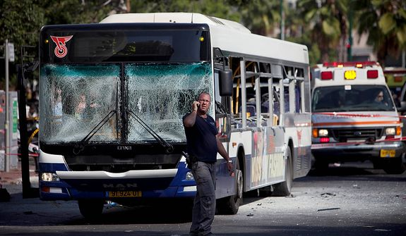 An Israeli security officer stands next to a blown up bus at the site of a bombing in Tel Aviv, Israel, Wednesday, Nov. 21, 2012. A bomb ripped through an Israeli bus near the nation's military headquarters in Tel Aviv on Wednesday, wounding several people, Israeli officials said. The blast came amid a weeklong Israeli offensive against Palestinian militants in Gaza. (AP Photo/Oded Balilty)
