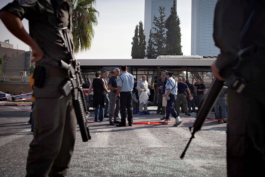 Israeli police and security personnel stand next to a destroyed bus at the site of a bombing in Tel Aviv, Israel, Wednesday, Nov. 21, 2012. A bomb ripped through an Israeli bus near the nation's military headquarters in Tel Aviv on Wednesday, wounding several people, Israeli officials said. The blast came amid a weeklong Israeli offensive against Palestinian militants in Gaza.(AP Photo/Dan Balilty)