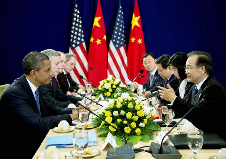 President Obama listens as Chinese Premier Wen Jiabao speaks across the table from him Tuesday during the East Asia Summit at the Peace Palace in Phnom Penh, Cambodia. (Associated Press)