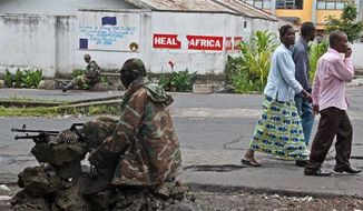 People walk past as M23 rebel soldier's take positions near the Heal Africa hospital in the center of Goma, Congo, Tuesday, Nov. 20, 2012. (AP Photo/Melanie Gouby)