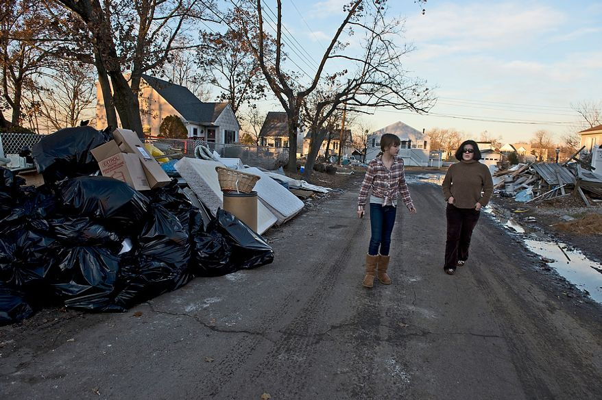 Abbi and Tiffany walk down a street in Union Beach, N.J. where people have emptied all of their belongings into the street after Hurricane Sandy on Wednesday, Nov. 21, 2012. They have donated items here that they collected in Project Keep Them Cozy, which Abbi, 12, and Andrew, 9, spearheaded. The family is spending their Thanksgiving up here volunteering. (Barbara L. Salisbury/The Washington Times)