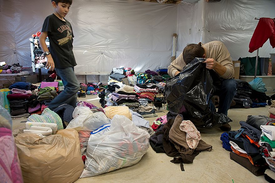 "Nine-year-old Andrew Audas walks through a pile of clothing as his dad Jim Audas goes through a trash bag of donated clothes while sorting through the many bags of donated clothing items for ""Project Keep Them Cozy,"" started by the Audas children to help victims of Hurricane Sandy. The family's unfinished basement room has become the home base for organizing and sorting all of the donations, which they will personally drive up to New Jersey this week. The family plans to stay up there through the Thanksgiving holiday to volunteer. This image was made Tuesday, Nov. 13, 2012. (Barbara L. Salisbury/The Washington Times)"