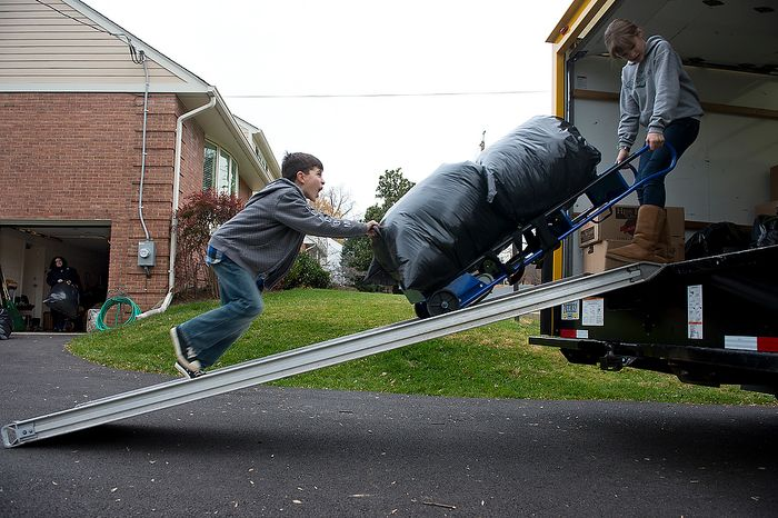 Andrew Audas, 9, left, and his sister Abbi, 12, roll a dolly carrying trash bags full of donated clothes up the ramp into their 12-foot rental truck, which they completely filled with donations for victims of Hurricane Sandy, while mom Tiffany gets more bags out of the garage, at left. The family loaded up the truck at their Bethesda, Md. home on Tuesday, Nov. 20, 2012 and will leave Wednesday morning for New Jersey, where they will donate all the items and then spend the next few days volunteering. (Barbara L. Salisbury/The Washington Times)