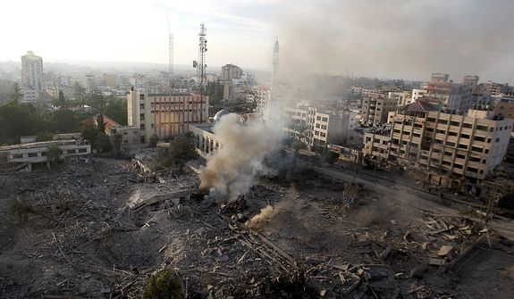 Smoke rises from the destroyed Hamas government complex known as Abu Khadra in Gaza City, early Wednesday, Nov. 21, 2012.  Israeli aircraft pounded Gaza with at least 30 strikes overnight, hitting government ministries, smuggling tunnels, a banker's empty villa and a Hamas-linked media office.  (AP Photo/Hatem Moussa)