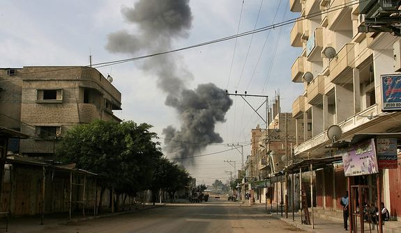 Smoke rises following an Israeli strike on smuggling tunnels along the border between Egypt and Rafah southern Gaza Strip, Wednesday, Nov. 21, 2012. Israeli aircraft pounded Gaza with at least 30 strikes overnight, hitting government ministries, smuggling tunnels, a banker's empty villa and a Hamas-linked media office.(AP Photo/Eyad Baba)