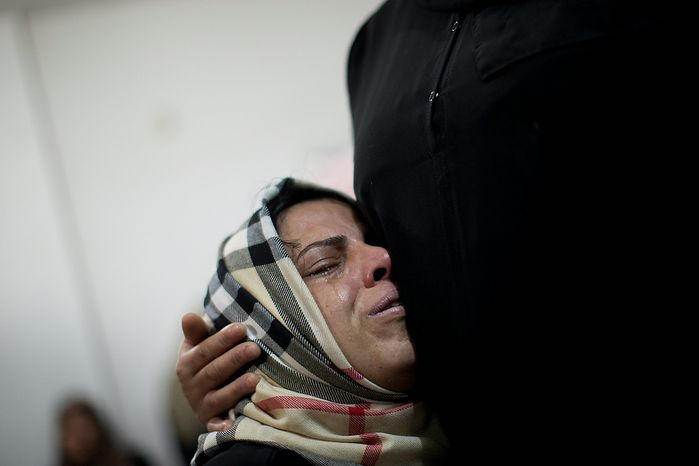 A Palestinian relative cries during the funeral of Mohammed al-Koumi in Gaza City, Wednesday, Nov. 21, 2012. Israeli airstrikes killed three Palestinian journalists in their cars on Tuesday, a Gaza health official and the head of the Hamas-run Al Aqsa TV said. Israel acknowledged targeting the men, claiming they had ties to militants. (AP Photo/Bernat Armangue)