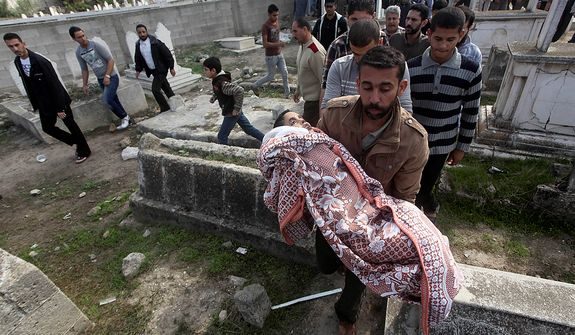 A Palestinian man carries the body of Mohammed Ashour, 10, killed the previous day in an Israeli air strike on Gaza City, during his funeral, Wednesday, Nov. 21, 2012. Israeli aircraft pounded Gaza with at least 30 strikes overnight, hitting government ministries, smuggling tunnels, a banker's empty villa and a Hamas-linked media office. (AP Photo/Ashraf Amra)