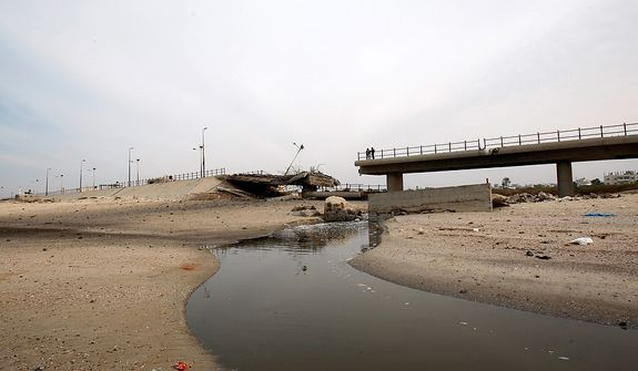 Palestinians look a destroyed beach bridge hit overnight in an Israeli air strike on the main beach road in Nuseirat, central Gaza Strip, Wednesday, Nov. 21, 2012. Israeli aircraft pounded Gaza with at least 30 strikes overnight, hitting government ministries, smuggling tunnels, a banker's empty villa and a Hamas-linked media office.(AP Photo/Adel Hana)