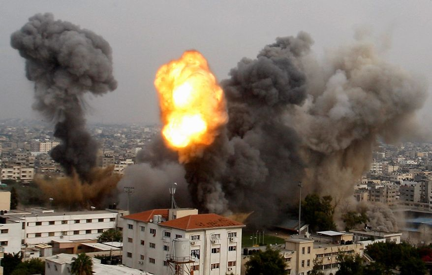 Smoke and a ball of fire are seen after an Israeli air strike in Gaza City, Wednesday, Nov. 21, 2012. Israeli aircraft pounded Gaza with at least 30 strikes overnight, hitting government ministries, smuggling tunnels, a banker's empty villa and a Hamas-linked media office.  (AP Photo/Hatem Moussa)