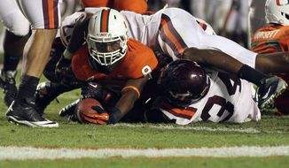 Virginia Tech's Ronny Vandyke (36) and Ksyhoen Jarrett (34) try to stop Miami's Duke Johnson (8) from scoring a touchdown during the second half of their NCAA college football game in Miami, Thursday, Nov. 1, 2012. Miami won 30-12. (AP Photo/J Pat Carter)