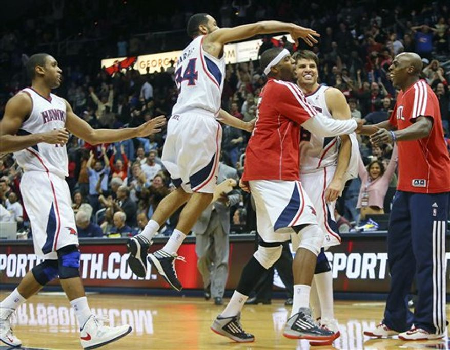 Atlanta Hawks' Josh Smith, third from right, grabs Kyle Korver, second from right, after Korver hit the winning 3-pointer against the Washington Wizards during overtime of their NBA game, Wednesday, Nov. 21, 2012, at Philips Arena in Atlanta. Hawks' Devin Harris (34) and Al Horford, left, join the celebration. The Hawks won 101-100. (AP Photo/Atlanta Journal-Constitution, Curtis Compton)
