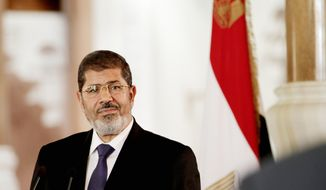 """Egyptian President Mohammed Morsi on Thursday granted himself far-reaching powers, prompting critics to call him the new """"pharaoh."""" A day earlier, he achieved a cease-fire to end eight days of fighting between Israelis and Palestinians. (Associated Press)"""