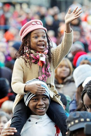 Irina Ahissou, 5, waves to Santa Claus as she sits on the shoulders of her brother Stely Ahissou, 12, during the parade in Philadelphia on Thursday. (Associated Press)