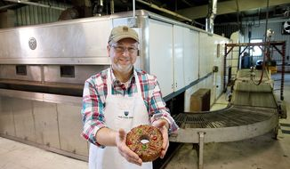 Ernie Polanskas, bakery manager at the Holy Cross Abbey in Berryville, Va., holds one of the 10,000 fruitcakes the abbey sells to buyers all over the world yearly. Mr. Polanskas does his baking in a huge industrial-sized oven the abbey bought back in the 1960s to bake bread before switching to fruitcake production. (Barbara L. Salisbury/The Washington Times)
