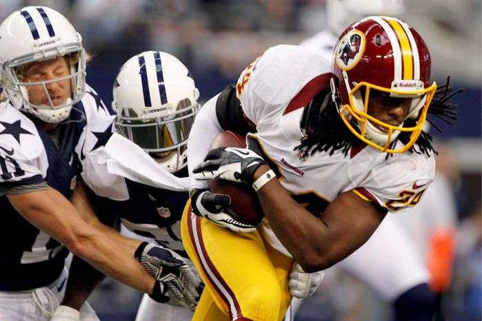 Washington Redskins strong safety DeJon Gomes (24) escapes tackles by Dallas Cowboys' Cole Beasley (11) and Dez Bryant, center, after recovering a fumble by Bryant in the first half of an NFL football game, Thursday, Nov. 22, 2012, in Arlington, Texas. (AP Photo/Tim Sharp)