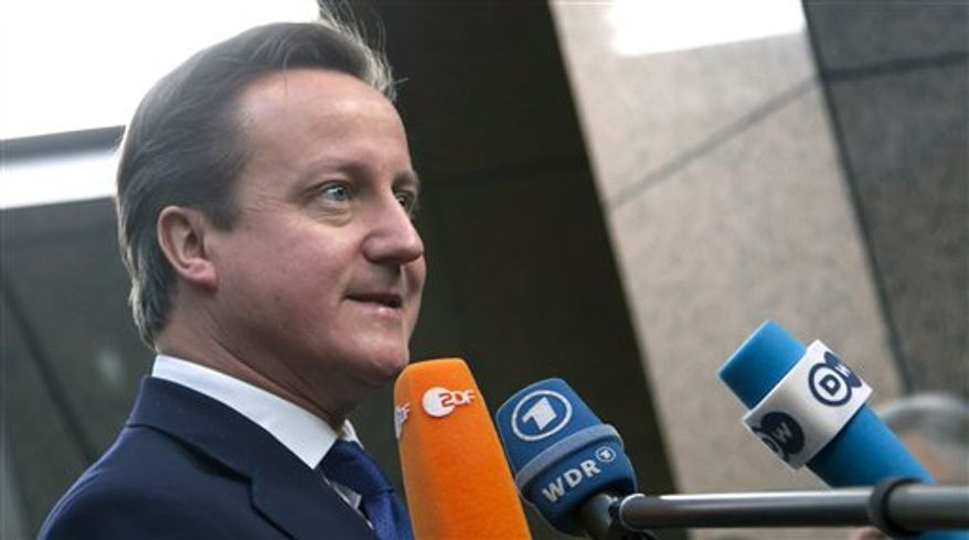 ** FILE ** British Prime Minister David Cameron speaks with journalists as he arrives for an EU summit at the EU Council building in Brussels on Thursday, Nov. 22, 2012. (AP Photo/Virginia Mayo)
