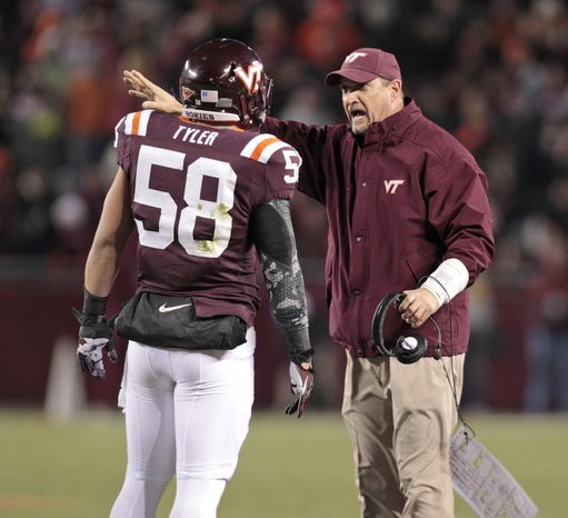 Virginia Tech defensive coordinator Bud Foster talks with Virginia Tech linebacker Jack Tyler (58) during the first half of a NCAA college football game in Blacksburg, Va., Thursday, Nov. 8, 2012. (AP Photo/Steve Helber)
