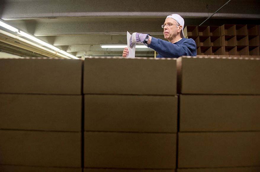 Surrounded by boxes of packaged fruitcakes, Brother Christopher Harmon puts shipping labels on more boxes to be shipped from the Holy Cross Abbey in Berryville, Va. on Monday, Nov. 19, 2012. The monks have been making fruitcakes for nearly 40 years and sell them as a means of making money for the day-to-day operations of the monastery. They bake from January to September, with Christmas being their busiest shipping time of year. (Barbara L. Salisbury/The Washington Times)