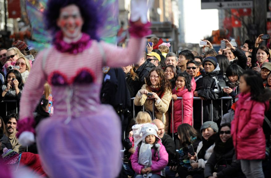 People watch the 86th annual Macy's Thanksgiving Day Parade,Thursday, Nov 22, 2012, in New York. The annual Macy's Thanksgiving Day Parade put a festive mood in the air in a city still coping with the aftermath of Superstorm Sandy. (AP Photo/ Louis Lanzano)