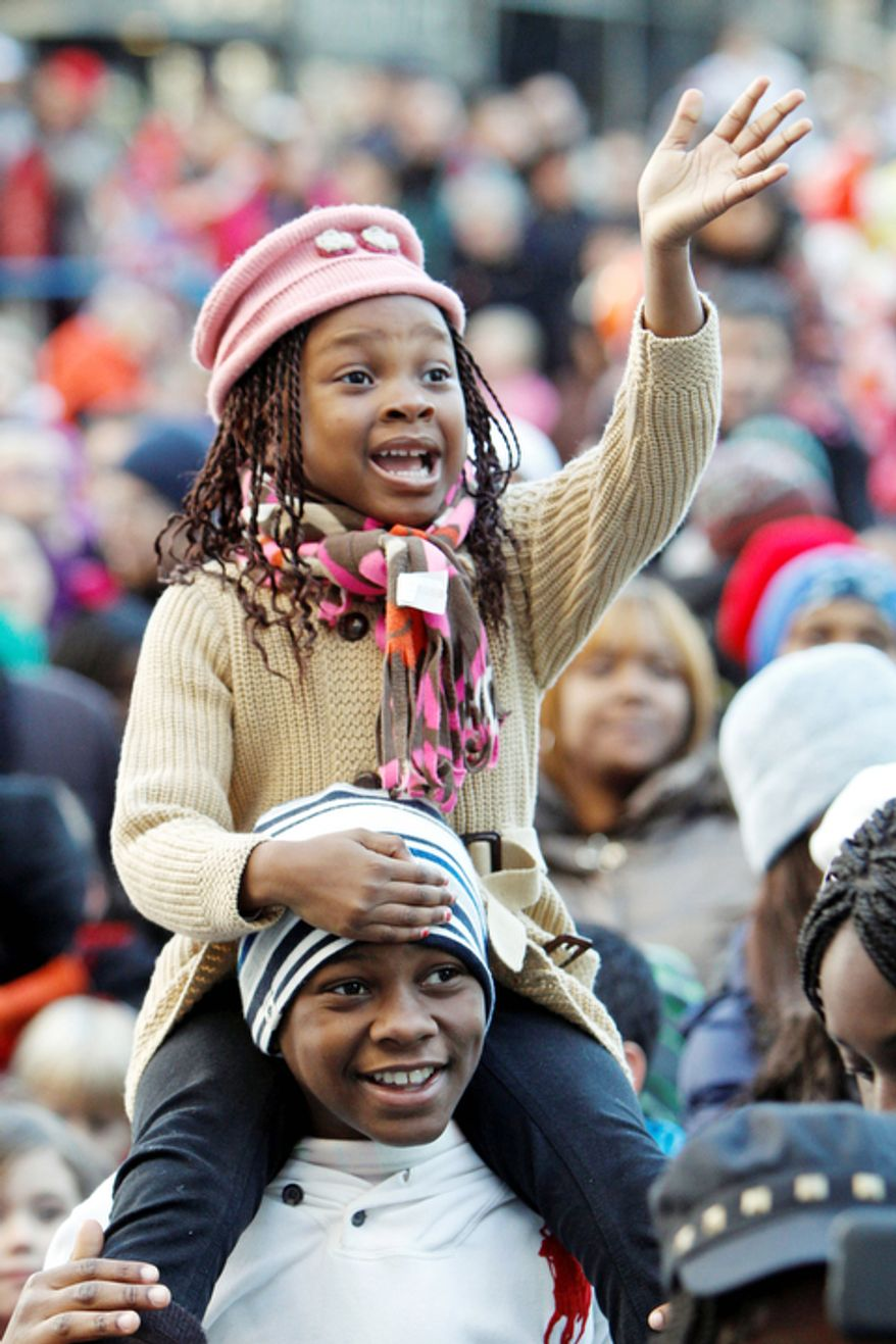 Irina Ahissou, 5, waves to Santa Claus as she sits on the shoulders of her brother Stely Ahissou, 12, during the 93rd annual Thanksgiving day parade, Thursday Nov. 22, 2012, in Philadelphia. (AP Photo/ Joseph Kaczmarek)