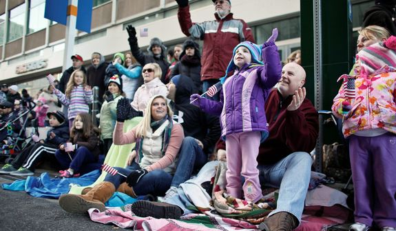 Spectators wave as they watch the 93rd annual Thanksgiving day parade, Thursday Nov. 22, 2012, in Philadelphia. New York, Chicago, and Detroit are also among the cities hosting holiday parades. (AP Photo/ Joseph Kaczmarek)
