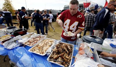 Curtis Early, of Alexandria, Va., selects pieces of turkey off a tailgate party spread outside Cowboys Stadium before an NFL football game between the Washington Redskins and the Dallas Cowboys, Thursday, Nov. 22, 2012, in Arlington, Texas. (AP Photo/Tim Sharp)