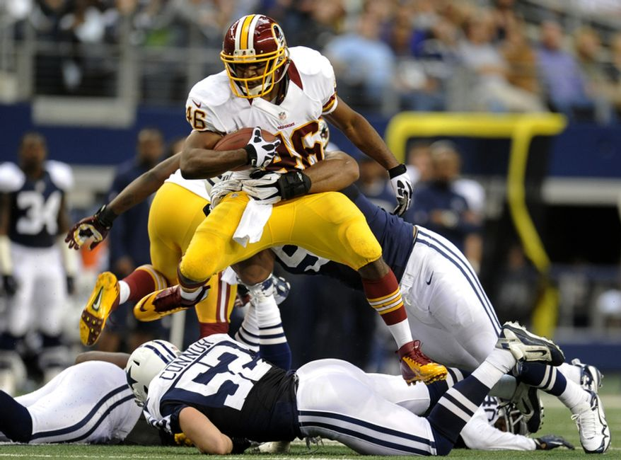 Washington Redskins running back Alfred Morris (46) leaps over Dallas Cowboys' Dan Connor (52) as he tries to escape a tackle by Jason Hatcher, rear, in the first half of an NFL football game, Thursday, Nov. 22, 2012, in Arlington, Texas. (AP Photo/Matt Strasen)