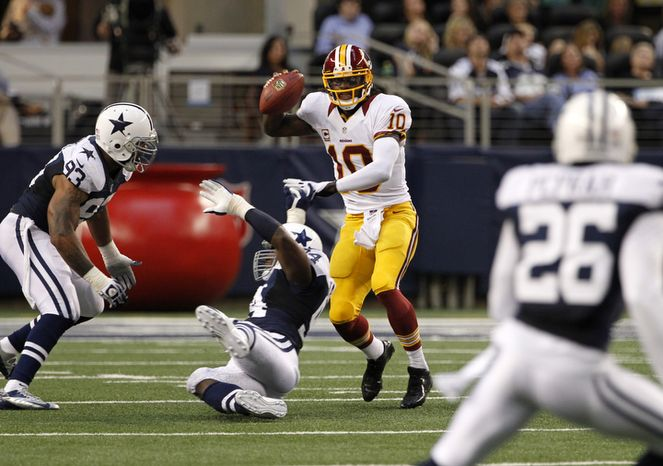 Dallas Cowboys outside linebacker Anthony Spencer (93) and DeMarcus Ware, bottom, pressure as Washington Redskins quarterback Robert Griffin III (10) avoids tackles in the first half of an NFL football game Thursday, Nov. 22, 2012, in Arlington, Texas. (AP Photo/Tim Sharp)