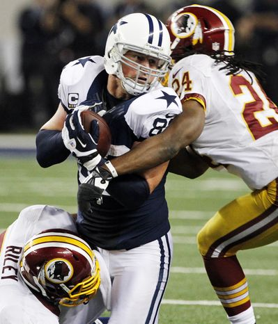Dallas Cowboys tight end Jason Witten (82) is stopped by Washington Redskins' Perry Riley, bottom, and DeJon Gomes (24) after grabbing a pass late in the second half of an NFL football game, Thursday, Nov. 22, 2012, in Arlington, Texas. The Redskins won 38-31. (AP Photo/Tim Sharp)