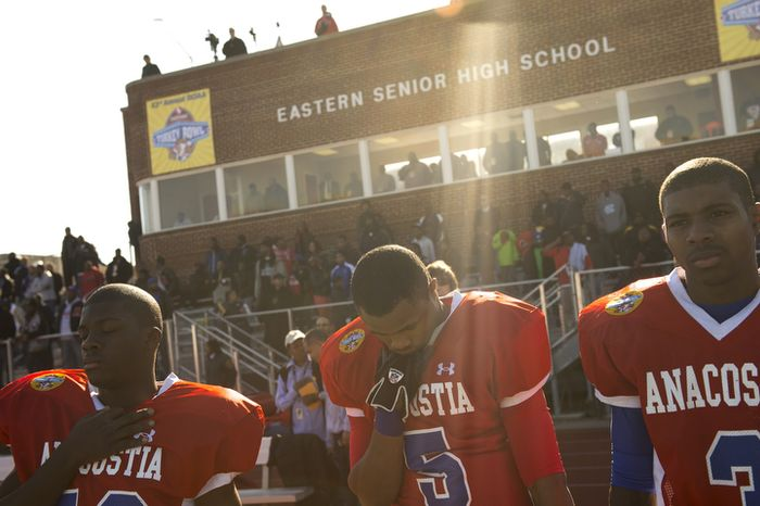 Anacostia High School's Yusuf Jones (5) bows his head during the playing of the National Anthem as they face Dunbar High School for the 43nd Annual DCIAA Turkey Bowl Varsity Football Championship at Eastern High School in Washington, D.C., Thursday, Nov. 22, 2012. This game, played between two District high school football teams is rich in tradition and always played on Thanksgiving Day, however this year's contest had a slight change in the last few days leading up to the game when Woodrow WIlson High School was disqualified because one the team's players was found to have been a resident of Maryland. Anacostia High School was chosen as an alternative. (Rod Lamkey Jr./The Washington Times)