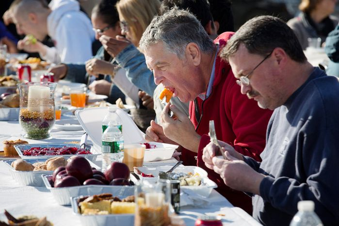 Carlos Buti, 45, center, and others share a free Thanksgiving dinner on Thursday, Nov. 22, 2012 in the Rockaway area of the Queens borough of New York, still recovering from Superstorm Sandy. (AP Photo/John Minchillo)