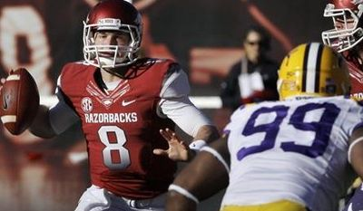 Arkansas quarterback Tyler Wilson (8) passes over LSU defensive end Sam Montgomery (99) as Arkansas offensive tackle Brey Cook, right, defends during the second quarter of an NCAA college football game in Fayetteville, Ark., Friday, Nov. 23, 2012. (AP Photo/Danny Johnston)