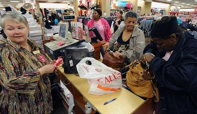 Linda Robinson (left) runs the register for shoppers Maxine Rocquemore (center) and Romona Rocquemore during early shopping on Nov. 22, 2012, at the Bealls Department Store in Nacogdoches, Texas. (Associated Press/The Daily Sentinel, Andrew D. Brosig)